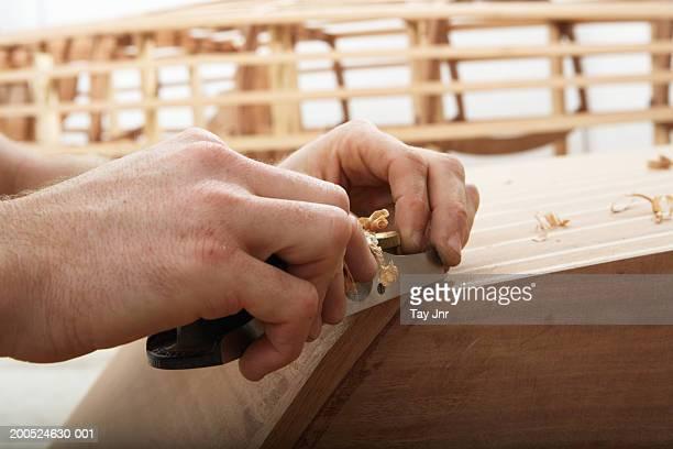 Giovane uomo costruire la barca nel workshop, close-up di mani
