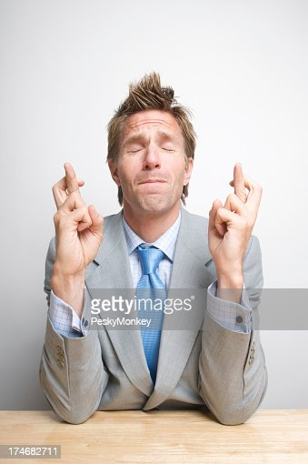 Young Man Businessman Crossing Fingers and Wishing Hard at Desk