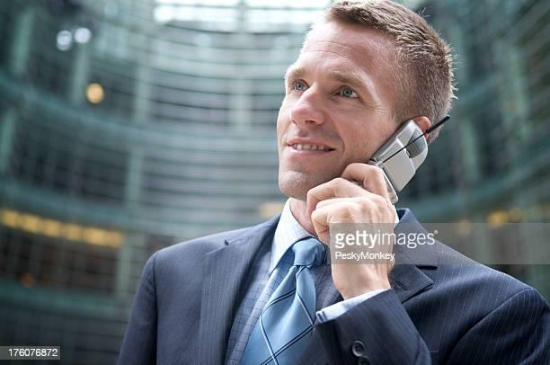 若い男性ビジネスマンが携帯電話で話しているフリップオフィスの背景