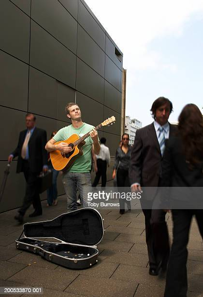 Young man busking with acoustic guitar in busy street