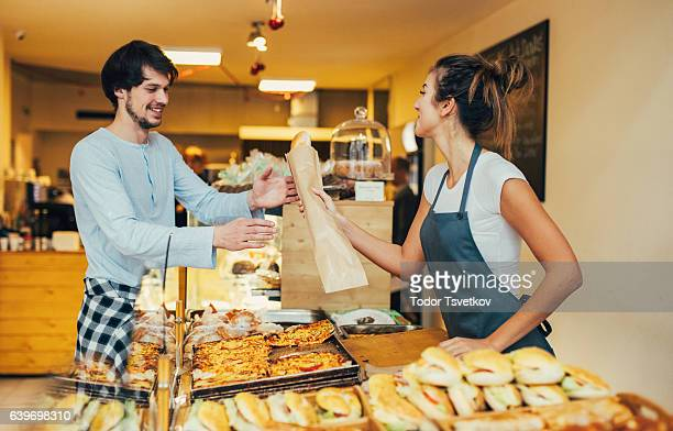 Young man buying bread at a bakery