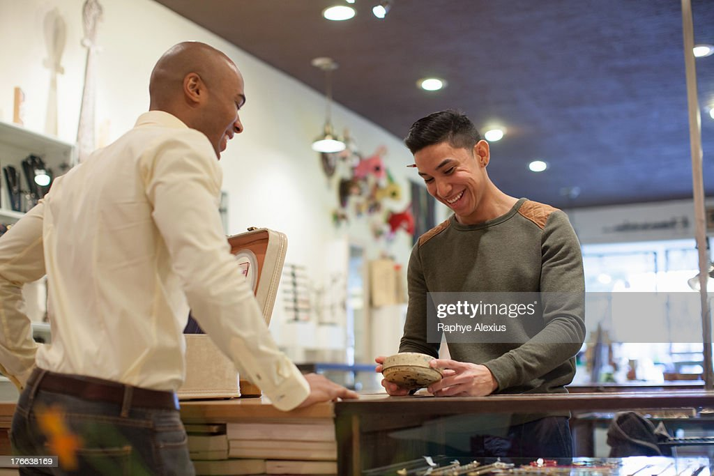 Young man buying item from shopkeeper in vintage shop : Stock Photo