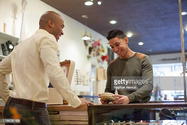 Young man buying item from shopkeeper in vintage shop