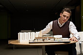 Young man by architectural model on table
