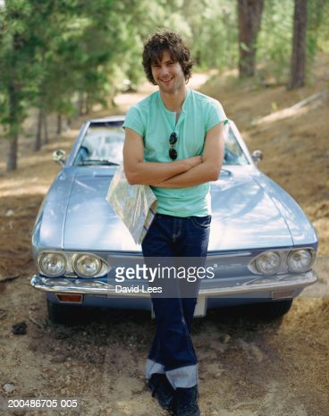 Young man by convertible car, smiling, portrait : Stock Photo