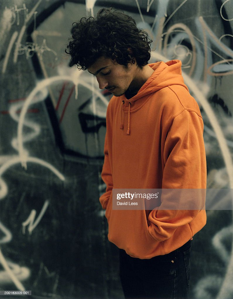 Young man by graffiti on wall : Stock Photo