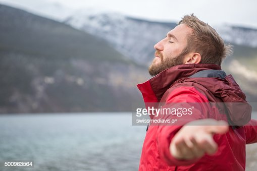 Young man by the lake arms outstretched for relaxation