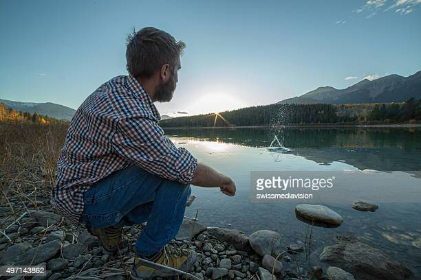 Young man by the lake at sunset skimming stones