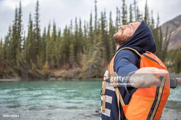 Junger Mann am Fluss Ausgestreckte Arme für positive emotion
