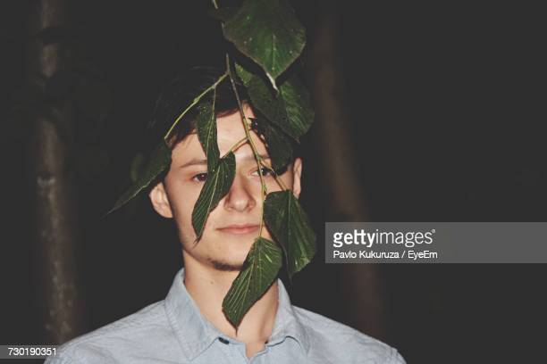 Young Man By Twig Of Plant At Night