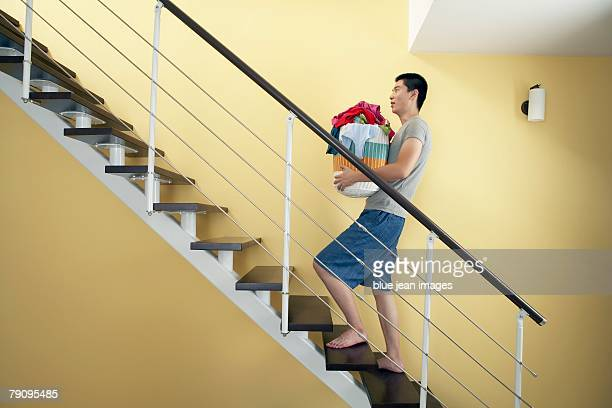 A young man carries laundry up the stairs.