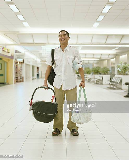Young man carrying baby carriage and bags in airport