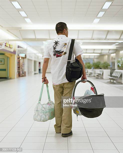 Young man carrying baby carriage and bags in airport, rear view