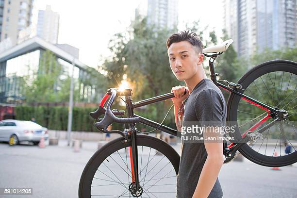 Young man carrying bicycle on shoulder