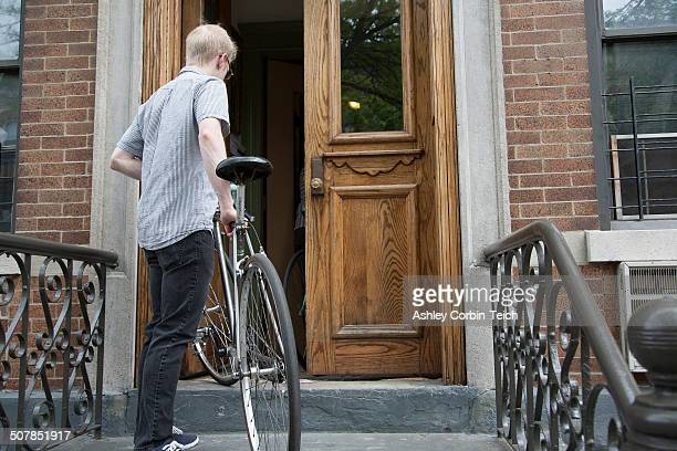 Young man carrying bicycle up steps to front door