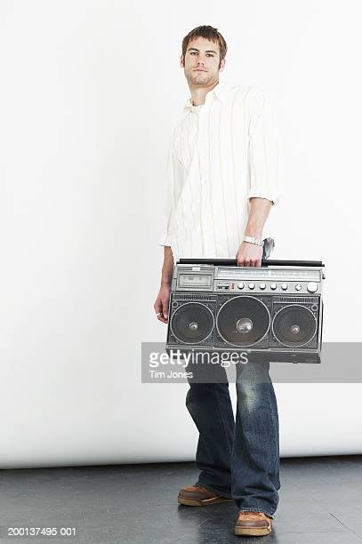 Young man carrying boom box, portrait