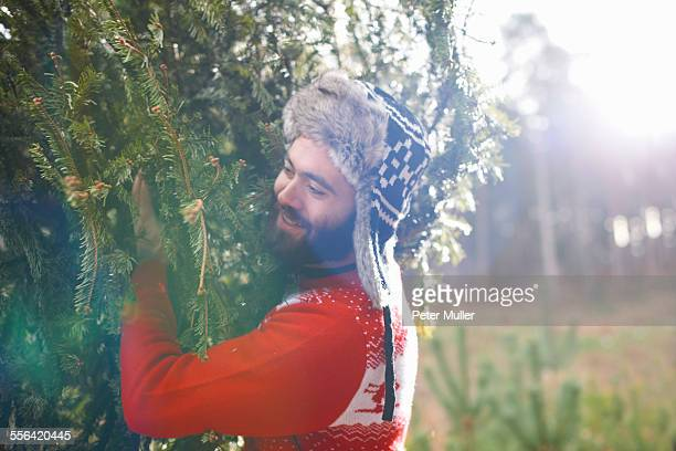 Young man carrying Christmas tree on shoulders in woods