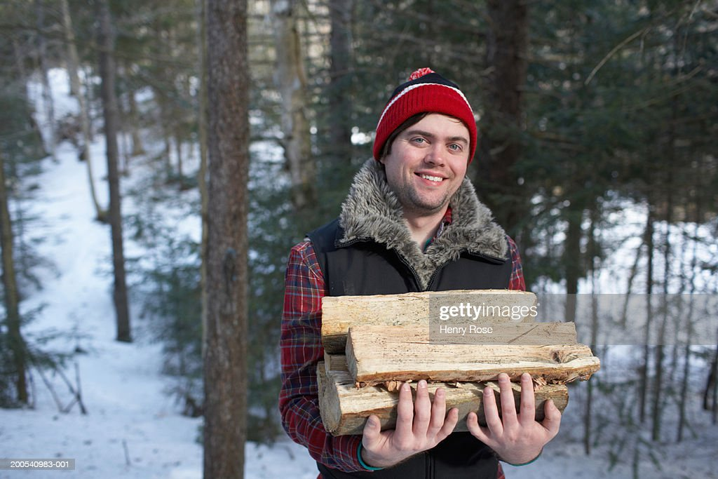 Young man carrying firewood, portrait : Stock Photo