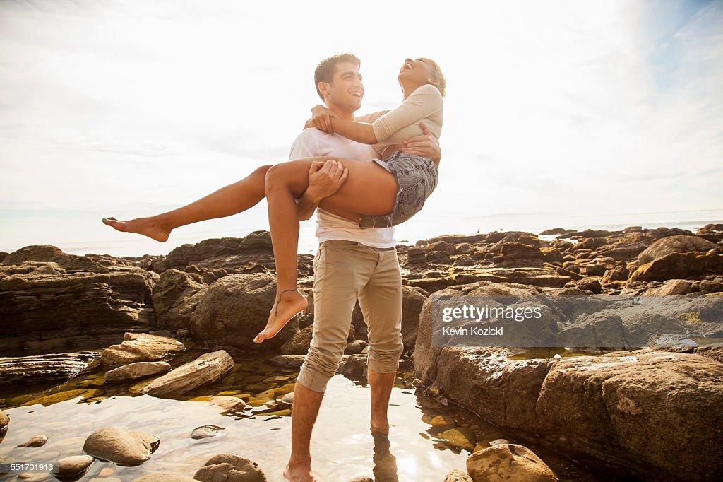 Young man carrying girlfriend across rock pool on beach