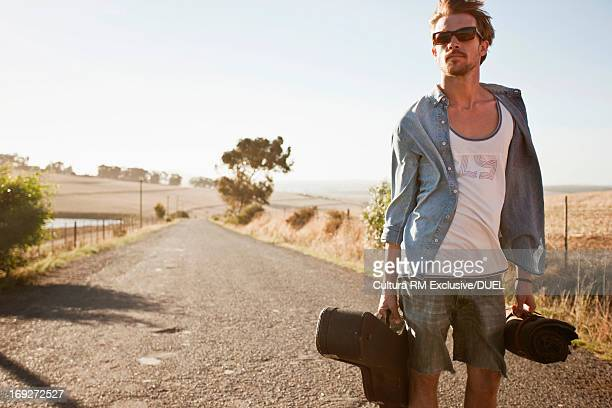 Young man carrying guitar case on empty road