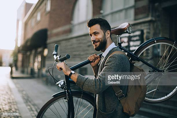 Young man carrying his bicycle