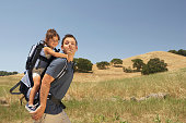 Young man carrying his daughter in a backpack outdoors