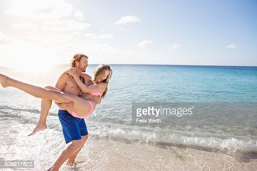 Young man carrying his girlfriend along sandy beach : Stock-Foto