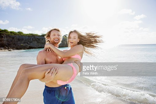 Young man carrying his girlfriend along sandy beach : Foto de stock