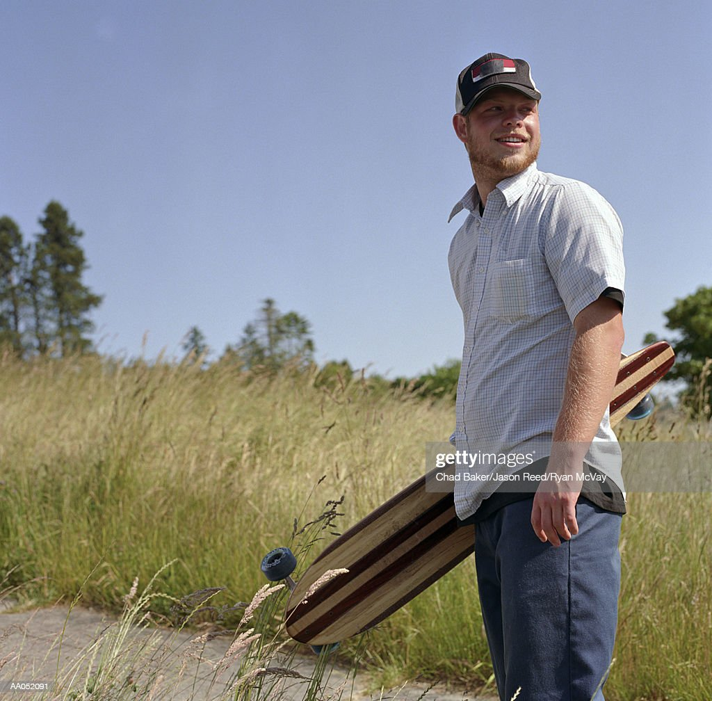 Young man carrying longboard, portrait : Stock Photo
