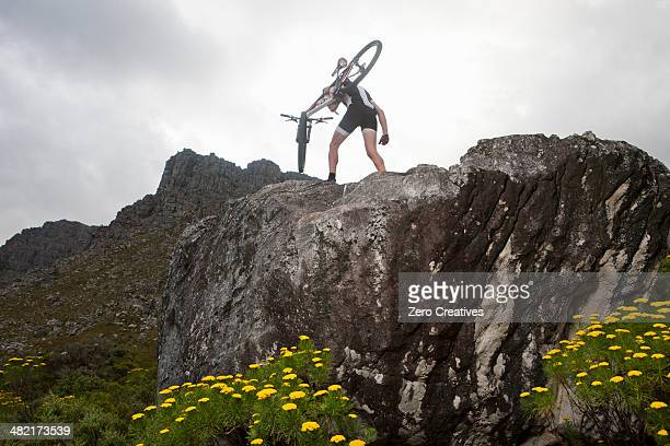 Young man carrying mountain bike on top of rock formation