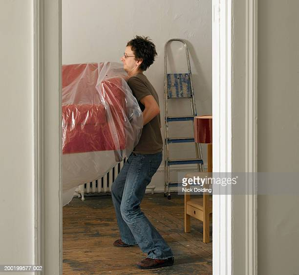 Young man carrying one end of sofa, view through doorway