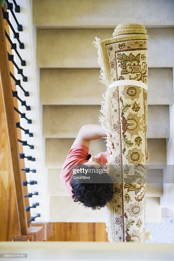 Young Man Carrying Rug Up Stairs, Overhead View : Stock Photo