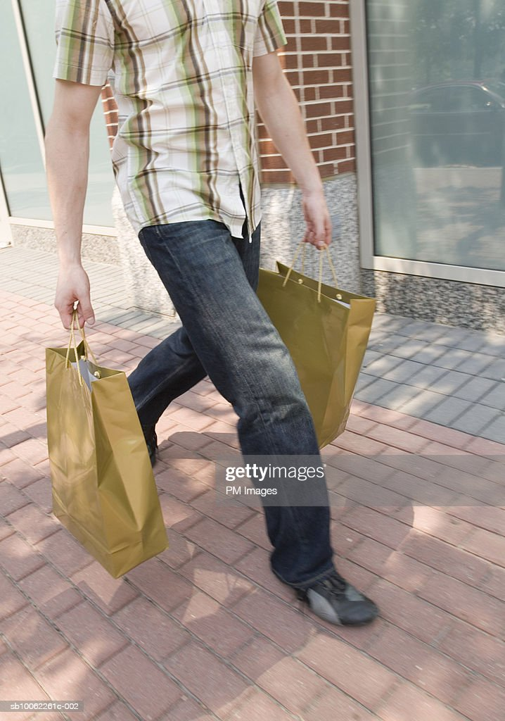 Young man carrying shopping bags in street : Stock Photo