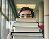 Young man carrying stack of books, close-up, portrait
