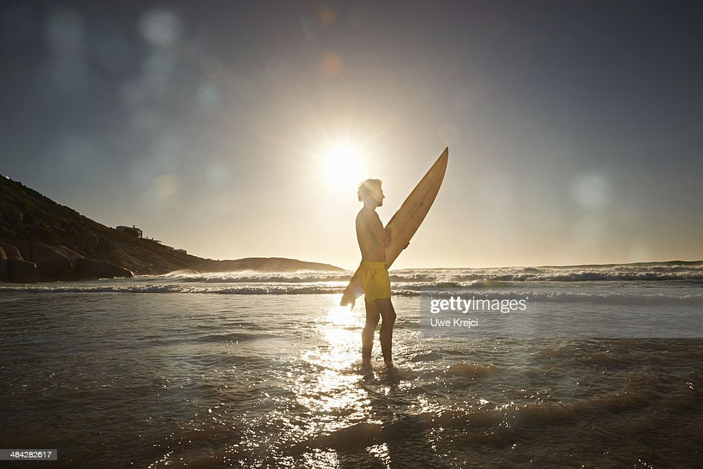 Young man carrying surfboard on beach