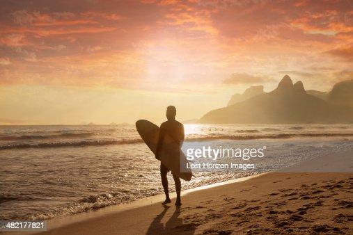 Young man carrying surfboard on Ipanema beach, Rio De Janeiro, Brazil