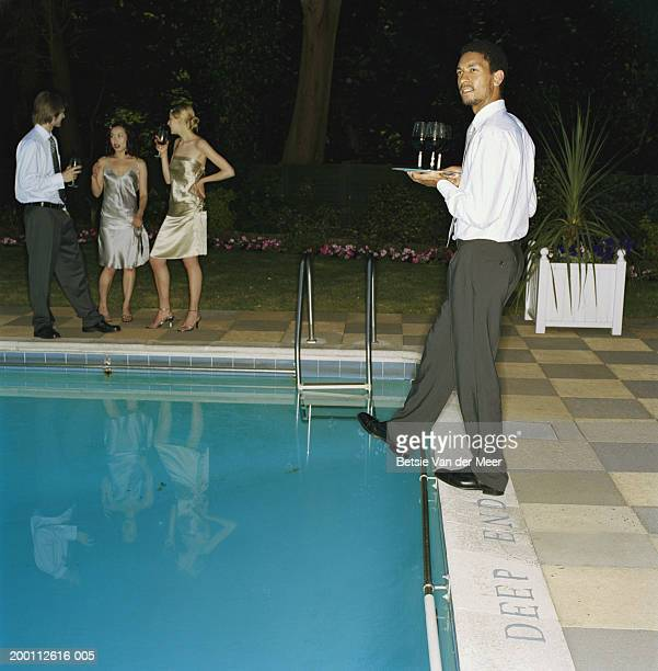 Young man carrying tray of drinks, taking step at edge of outdoor pool