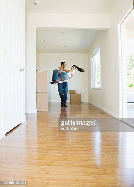 Young man carrying young woman in empty living room, smiling