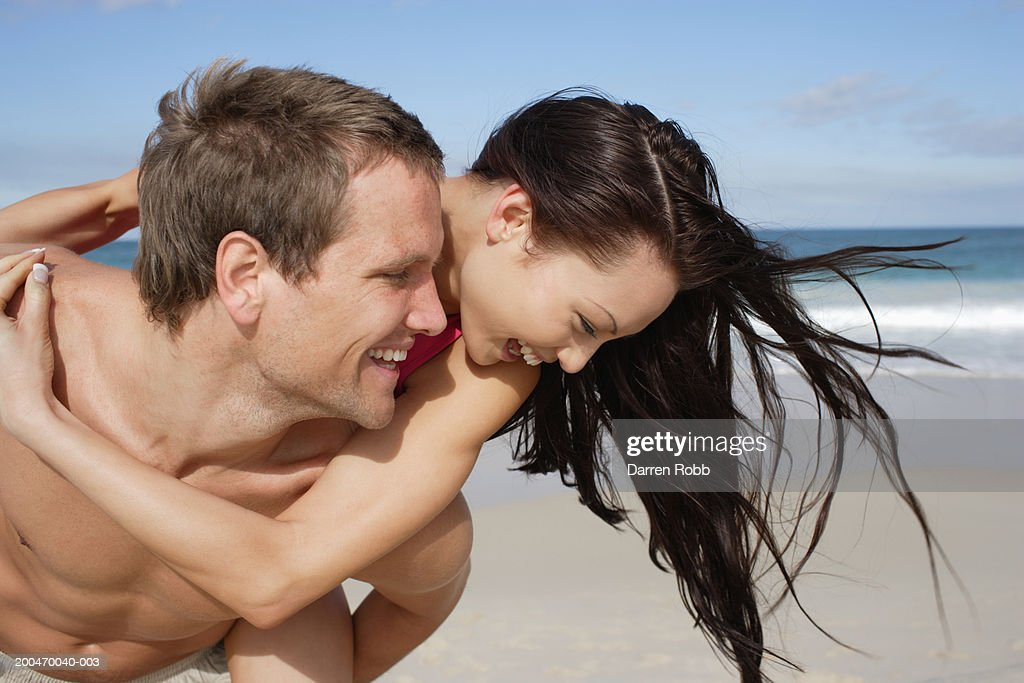 Young man carrying young woman on beach : Stock Photo