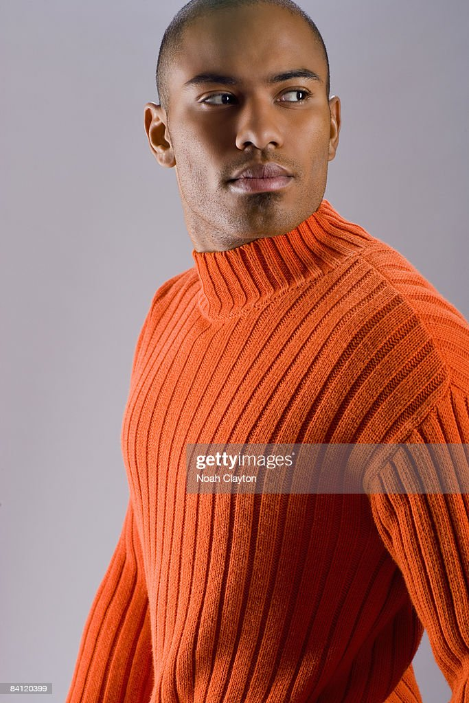 Young man casually dressed in orange sweater : Stock Photo