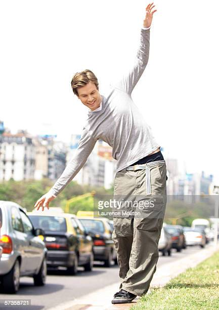 Young man catching balance as he walks on curb