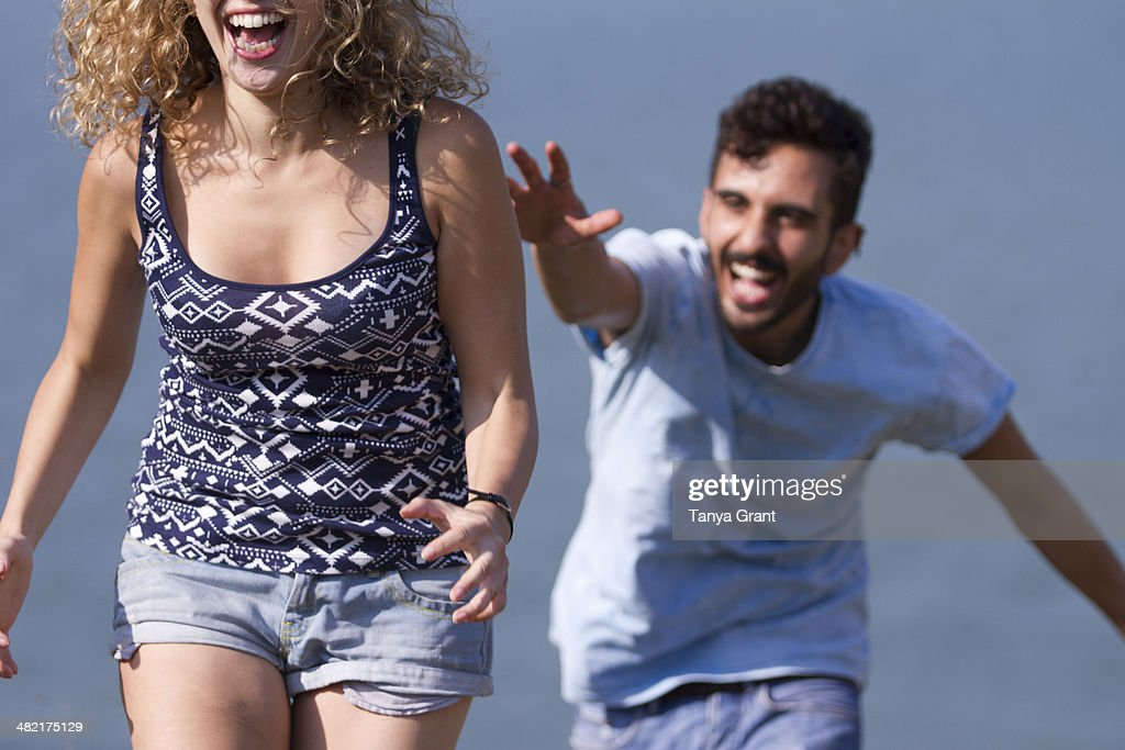 Young man chasing woman, laughing