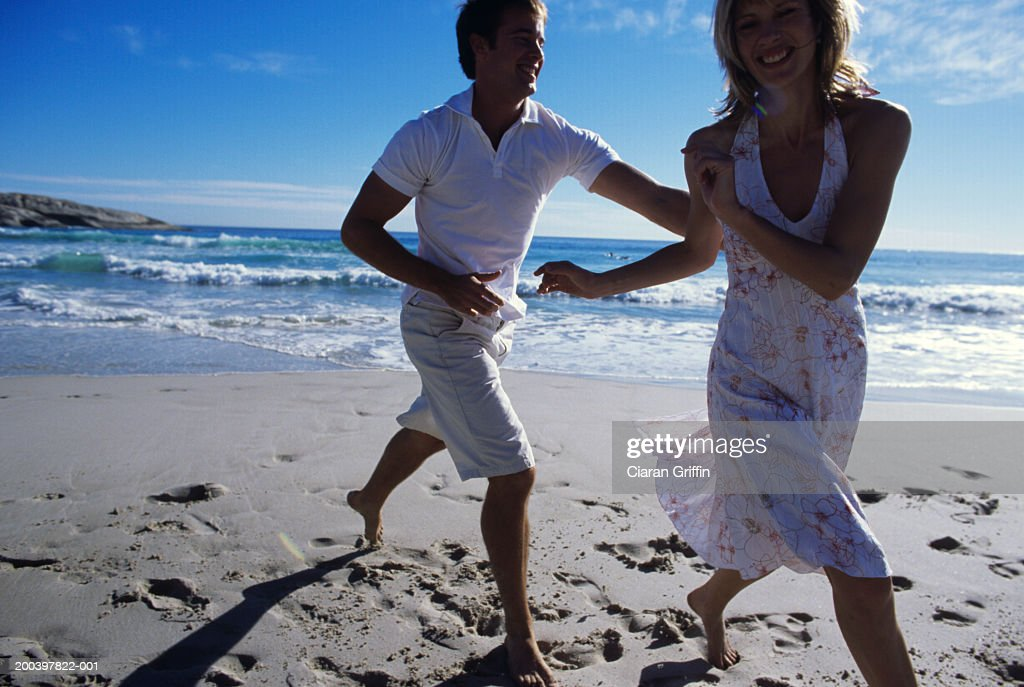Young man chasing woman on beach : Stock Photo