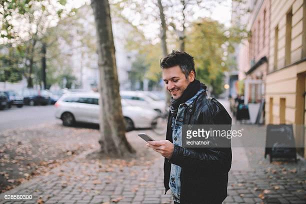 Young man checking cellphone in Berlin Prenzlauer Berg