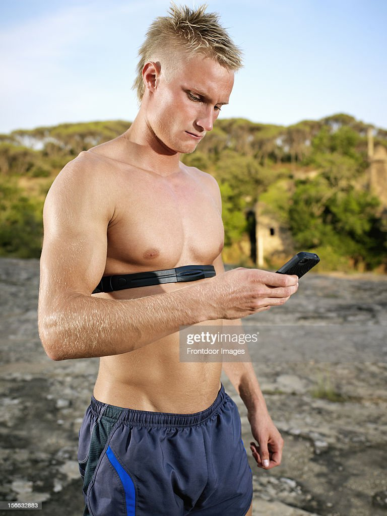 Young man checking heart rate on smart phone : Stock Photo
