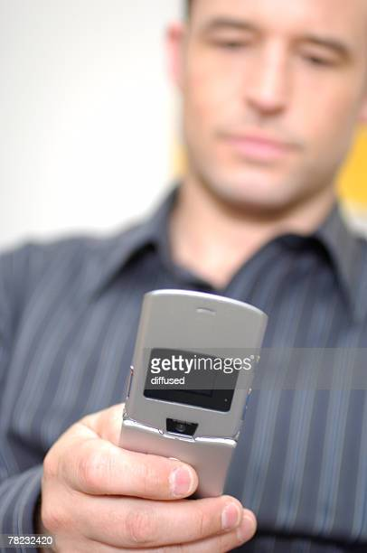 young man checking his mobile phone for text messages