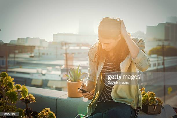 Young man checking his smartphone on urban rooftop