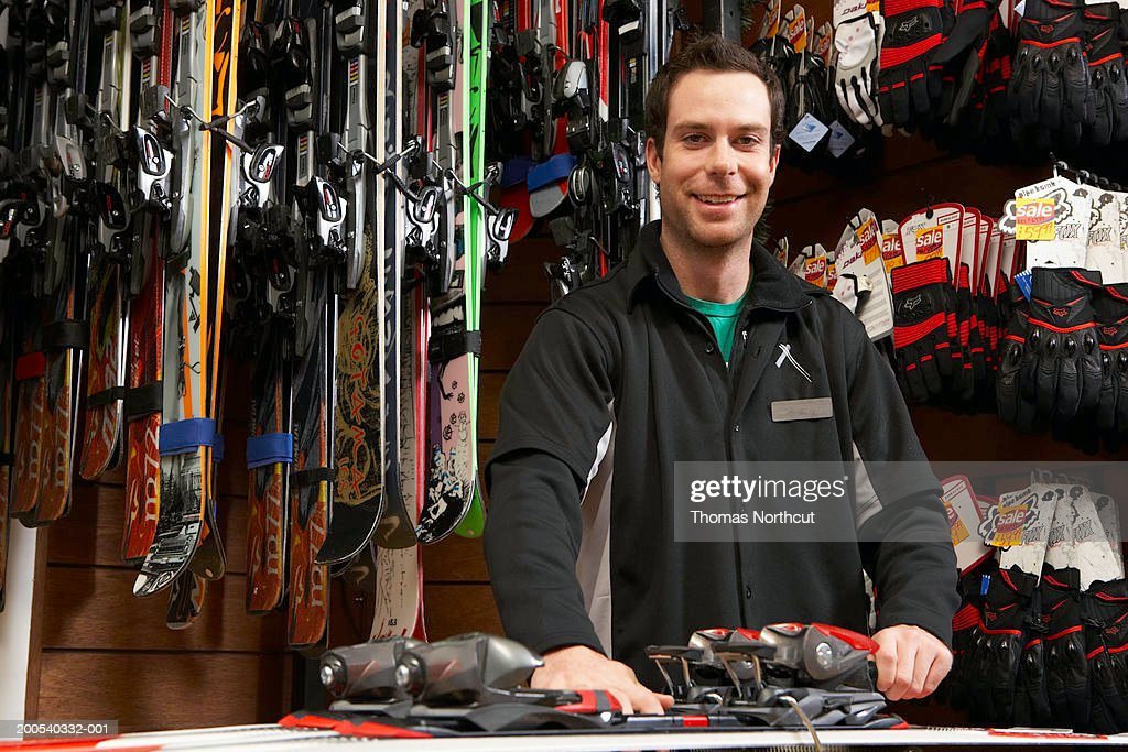 Young man checking skis and bindings in sports shop, portrait