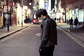 Young man checks phone as he crosses the road