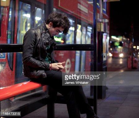 Young man checks phone at bus stop